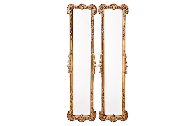 A pair of skinny, eclectic, gold-leaf oversized mirrors.