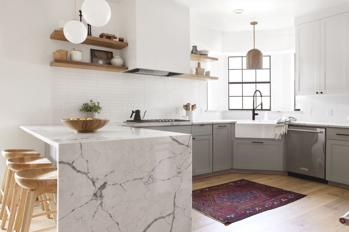 A kitchen with gray cabinets, natural wood shelves, and white marble countertops
