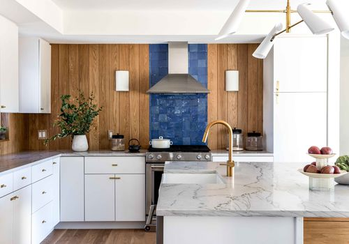 Modern kitchen with wood panelling, blue tiles, and marble counters