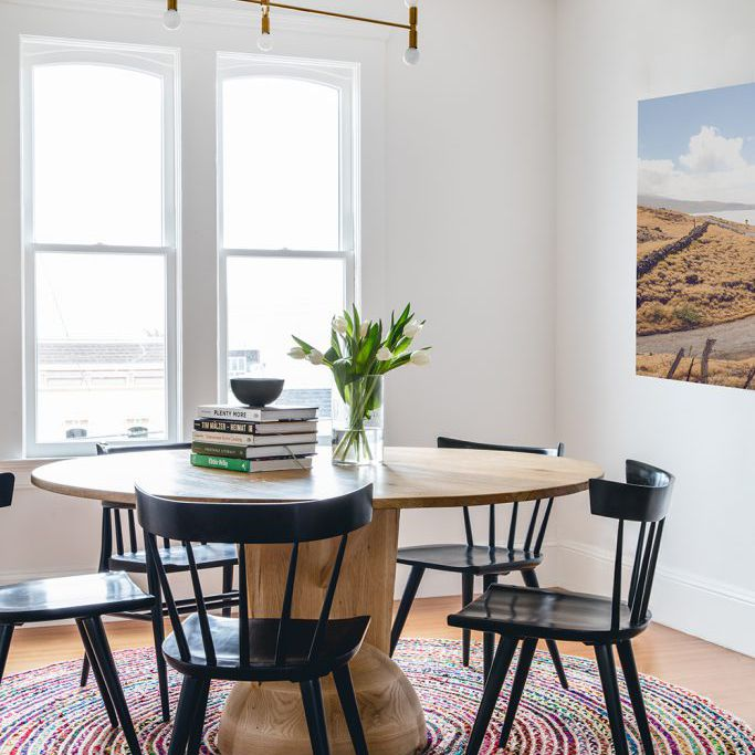 Small dining table with round woven rug underneath.