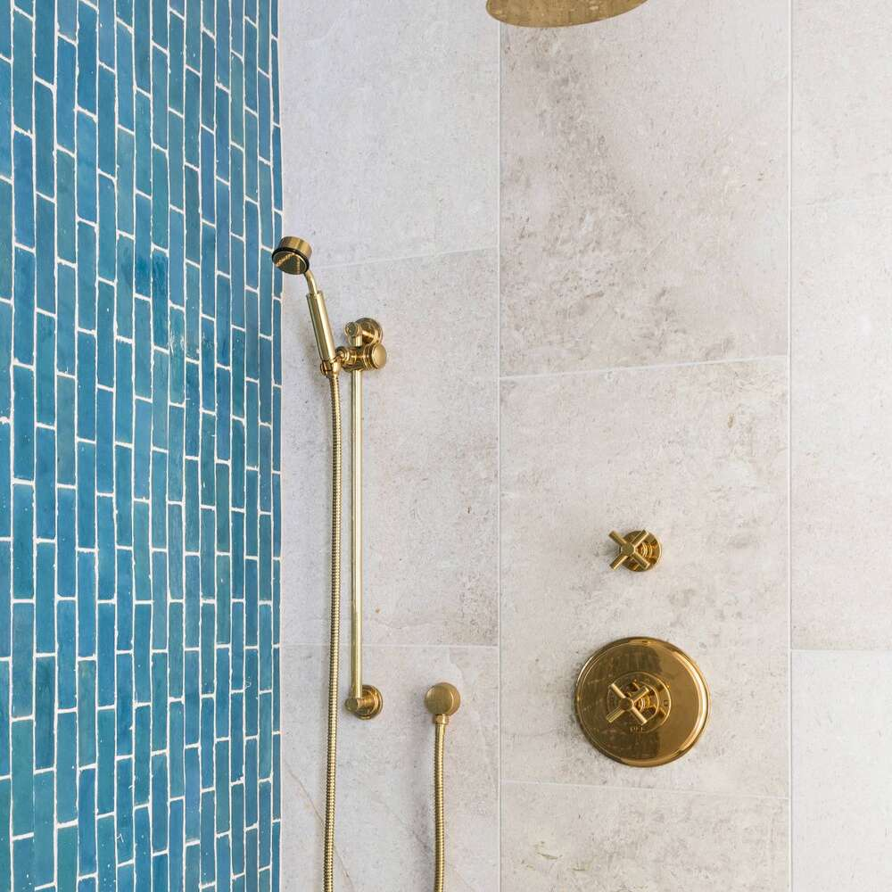 A shower with a blue tile accent wall