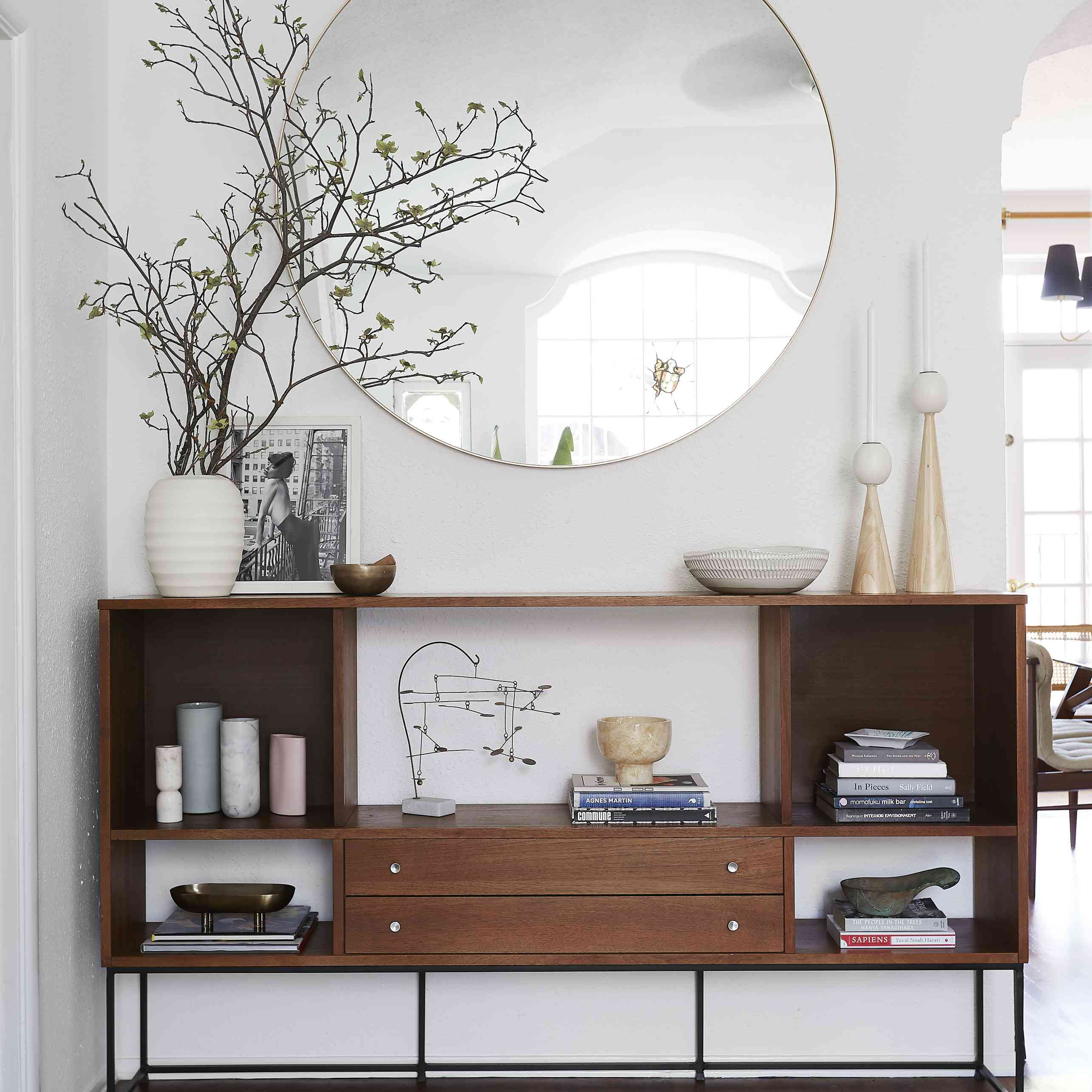 living room vignette with credenza and oversize round mirror