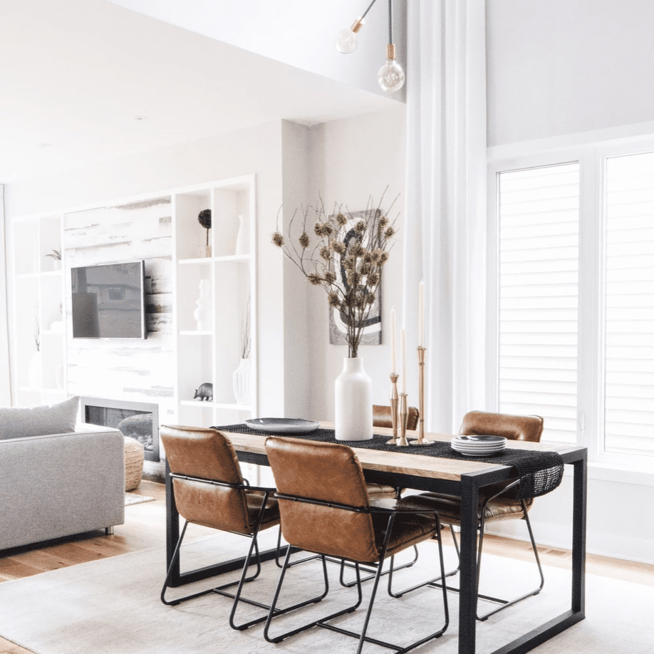 A small dining room table with a sleek black table runnre