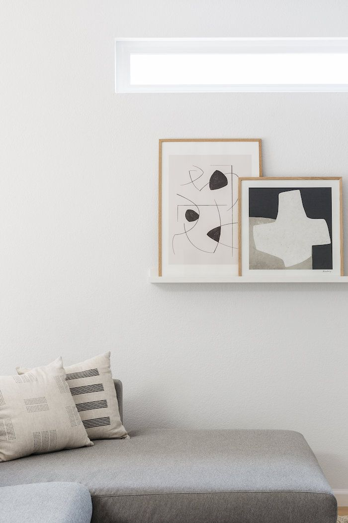 neutral living room with floating shelves holding abstract artwork