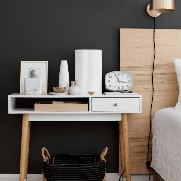 A bedroom with a small desk used as a nighstand