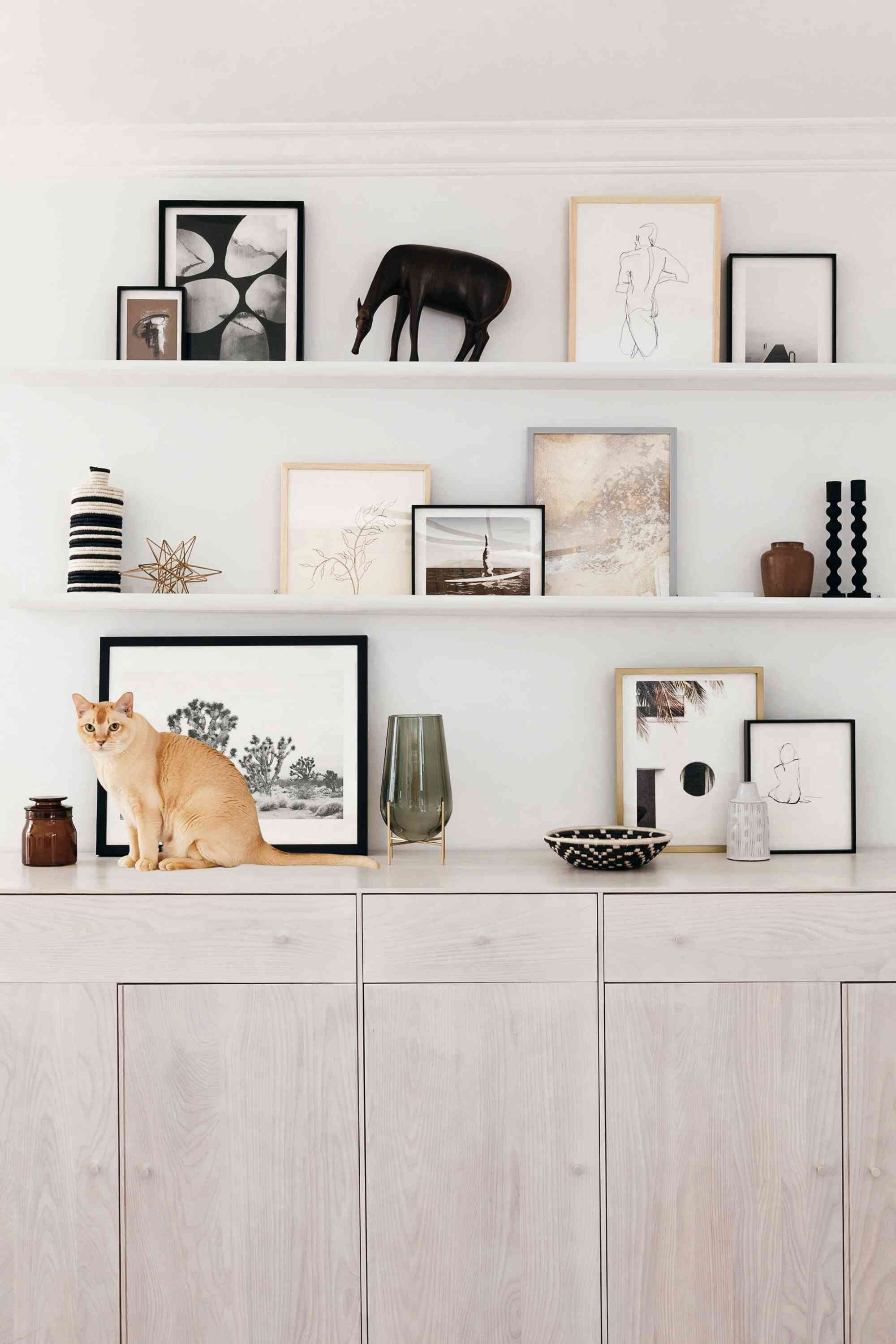 Art display above a sideboard with photo ledges
