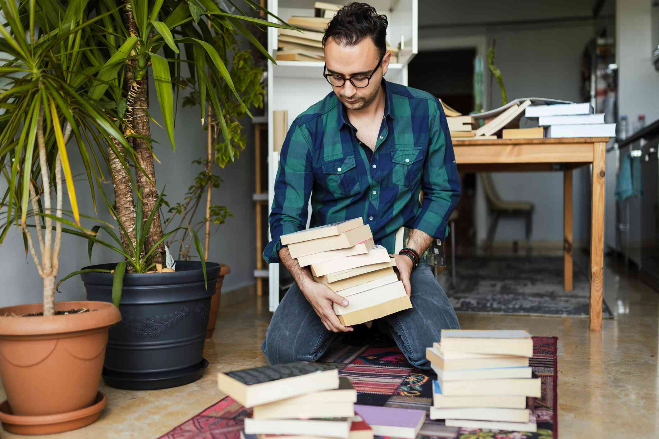 Young man in glasses rearranges pile of books
