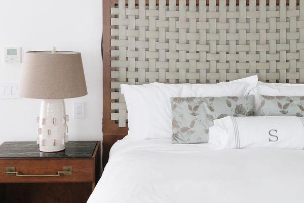 Monogramed pillow on white bed.