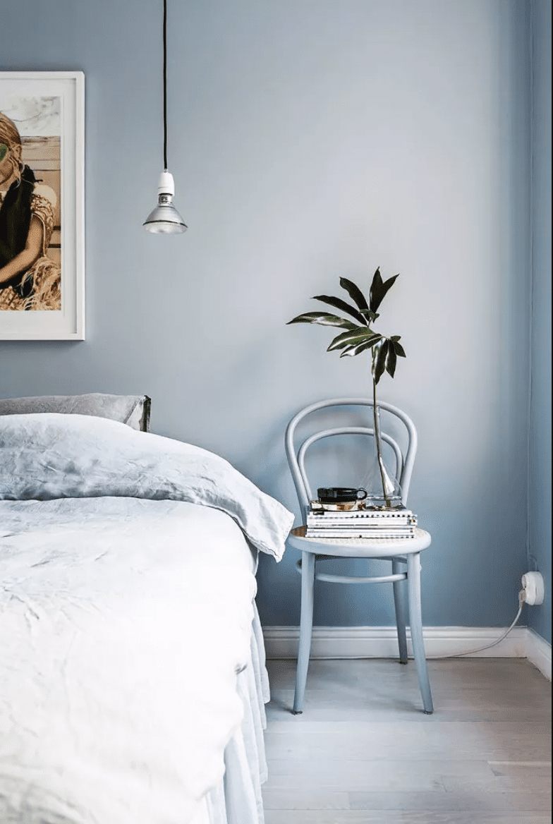 Blue bedroom with hanging, exposed light bulb