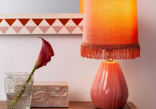 Una lámpara de mesa rosa en una consola con una orquídea rosa en un jarrón de vidrio sentado frente a una caja decorativa.