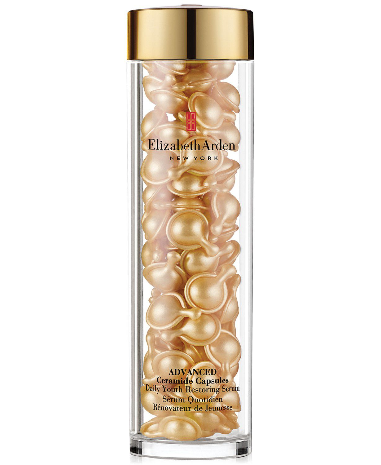 A tall glass cylinder full of gold tone ceramide filled capsules.