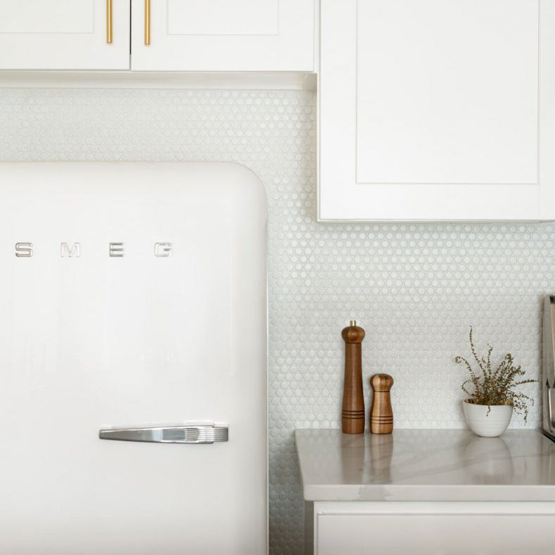 An all-white kitchen with walls lined with penny tiles