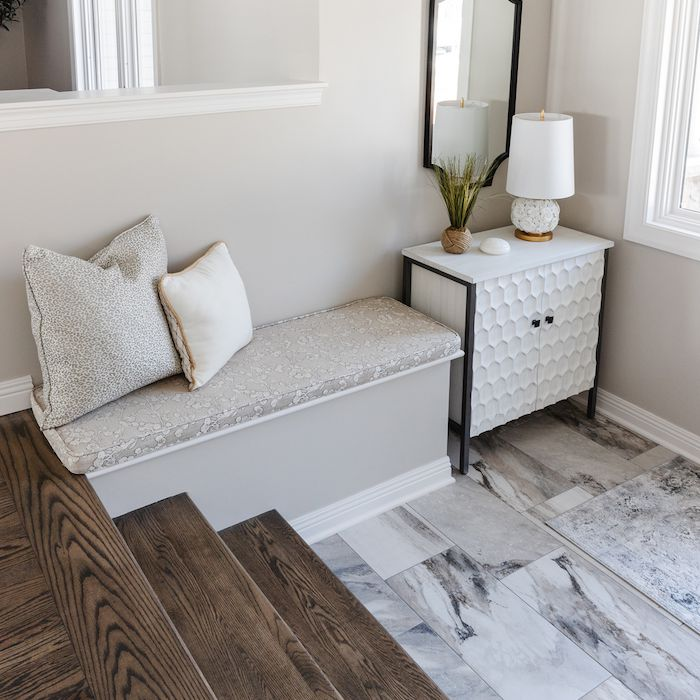 entryway with tile marble floor, leading to small stairway with built in nook and small white side table