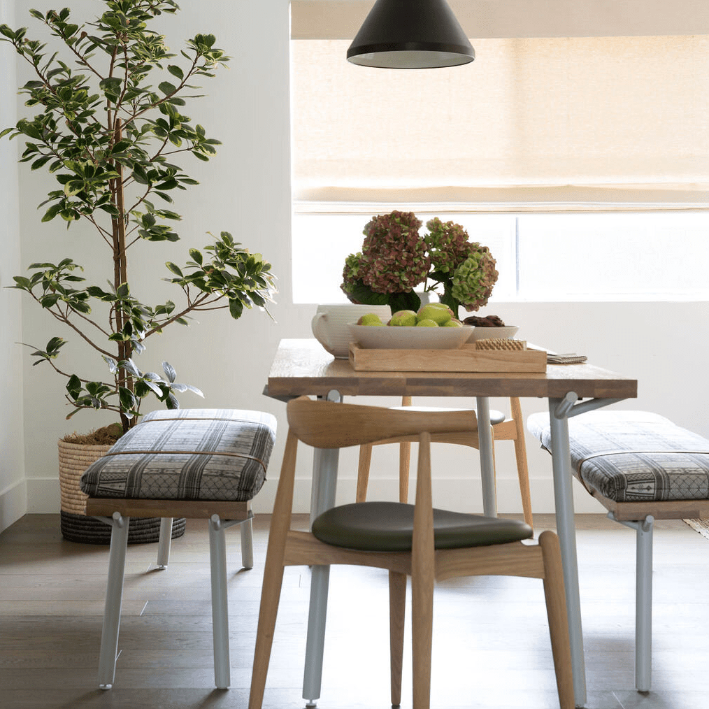 A wooden dining room table with legs that have been painted light blue