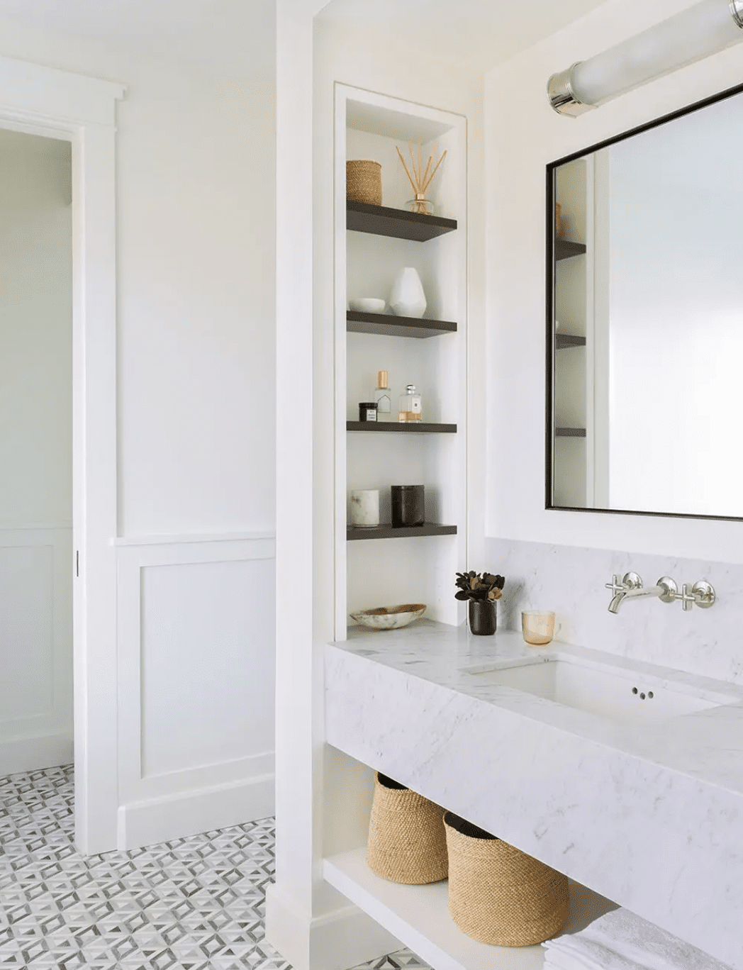 A small primary bathroom with shelves tucked into the wall and below the sink