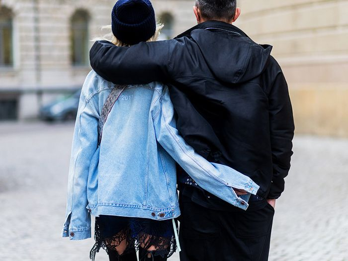 a couple walking arm in arm seen from behind