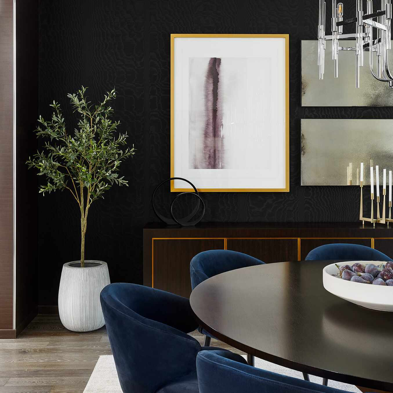 A dining room decorated with black walls, a black table, navy chairs, and a crisp white rug