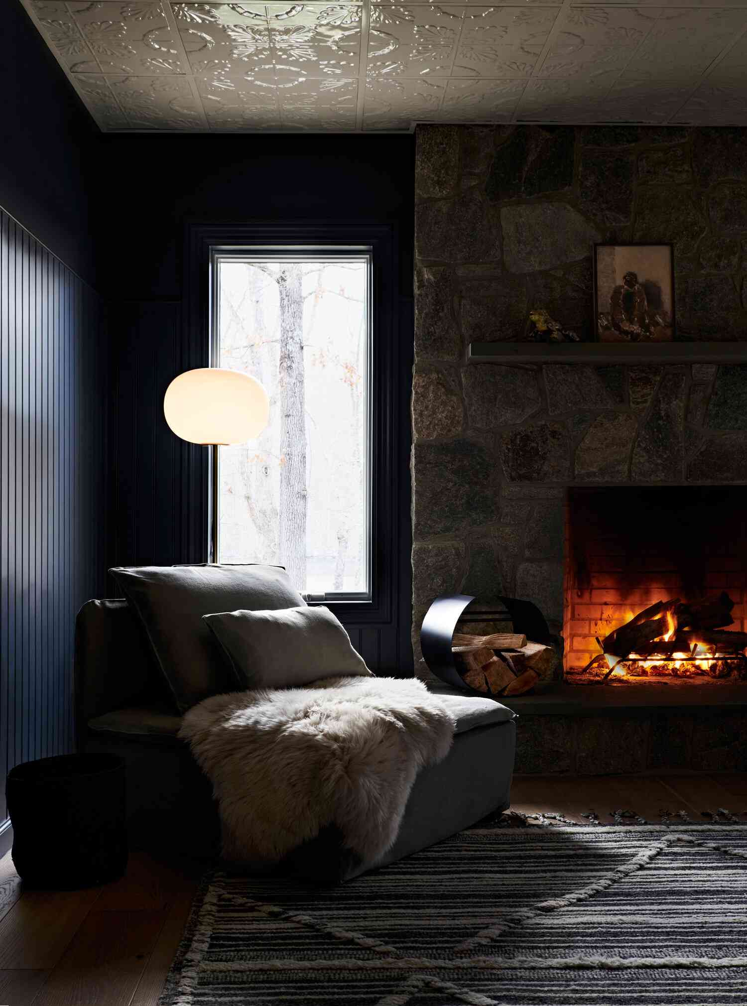 Cozy living room with dark furniture and a lit fire
