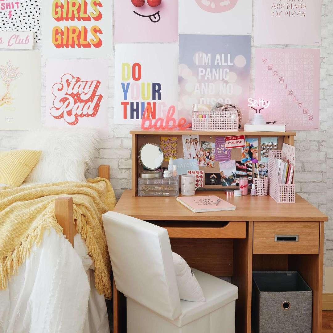 Gallery wall of pink art in dorm room.