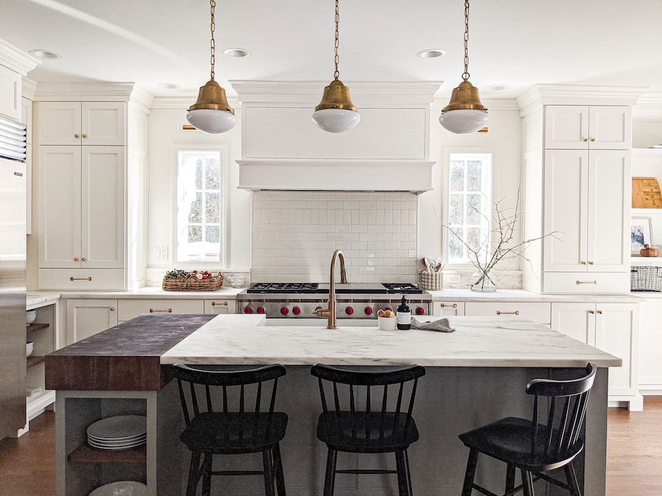 White kitchen with marble countertops.