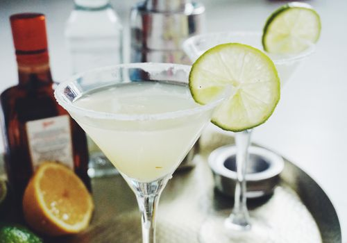 Margarita in a martini glass with a lime wheel on the side.