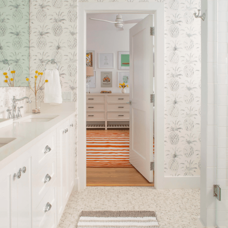 Tiled bathroom with pineapple-printed wallpaper