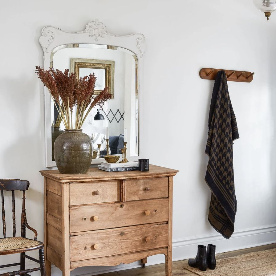 entryway with silver ornate mirror and dresser