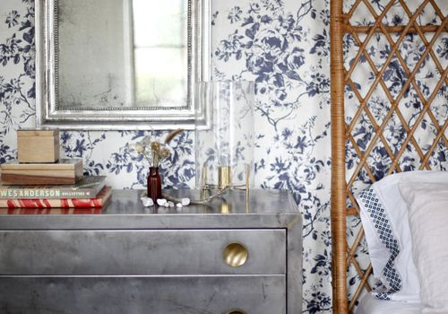 bedroom with blue and white toile wallpaper a gray dresser and wicker bedframe