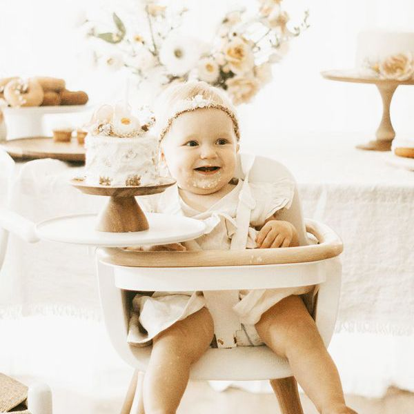 a baby in a highchair with a small cake on the tray