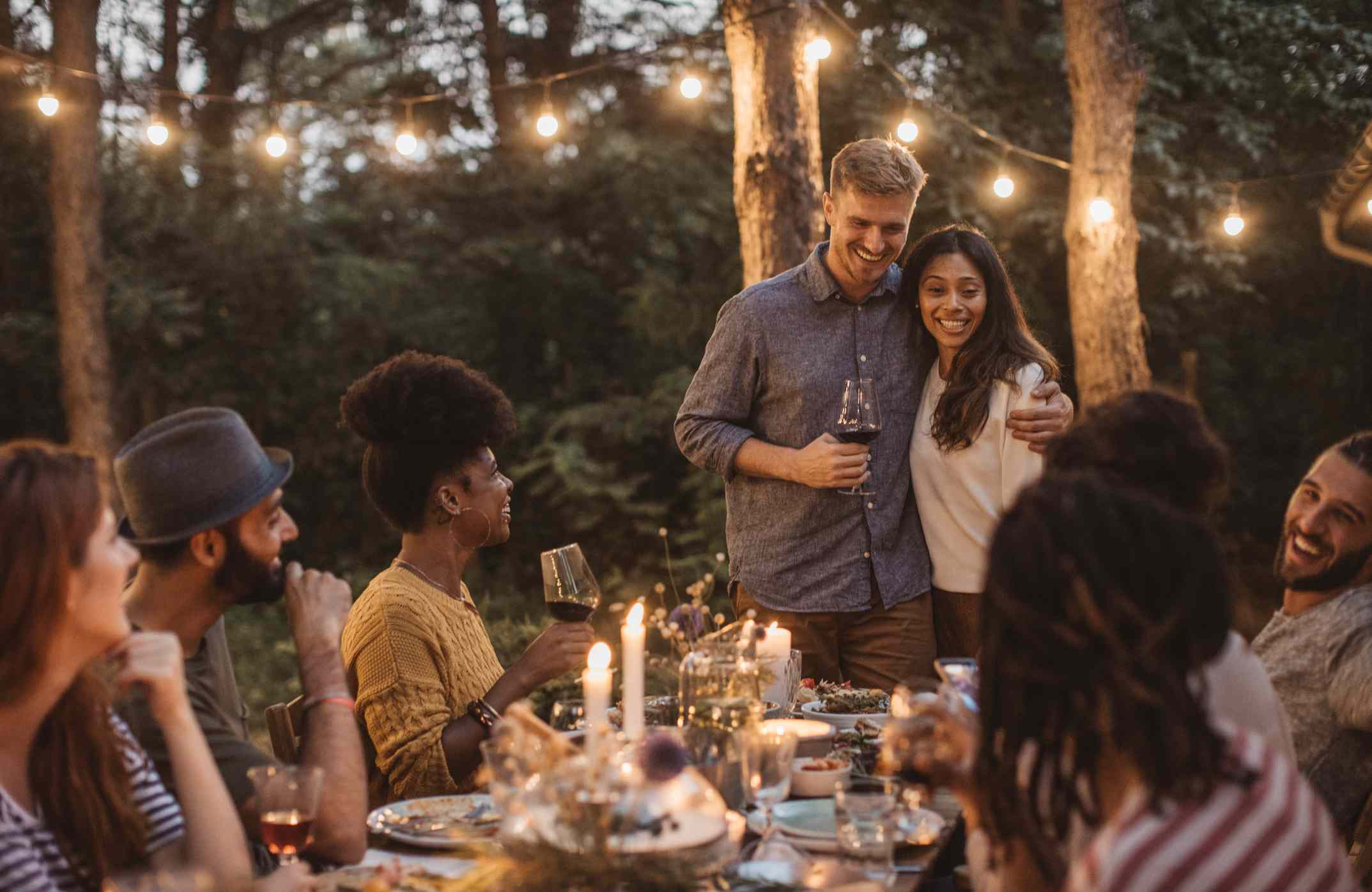 Young couple hosting a dinner party outdoors