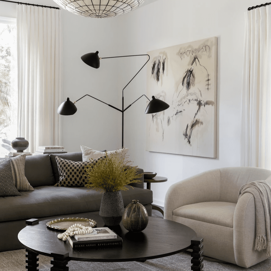 A corner with an ivory painting, ivory armchair, and ivory chandelier