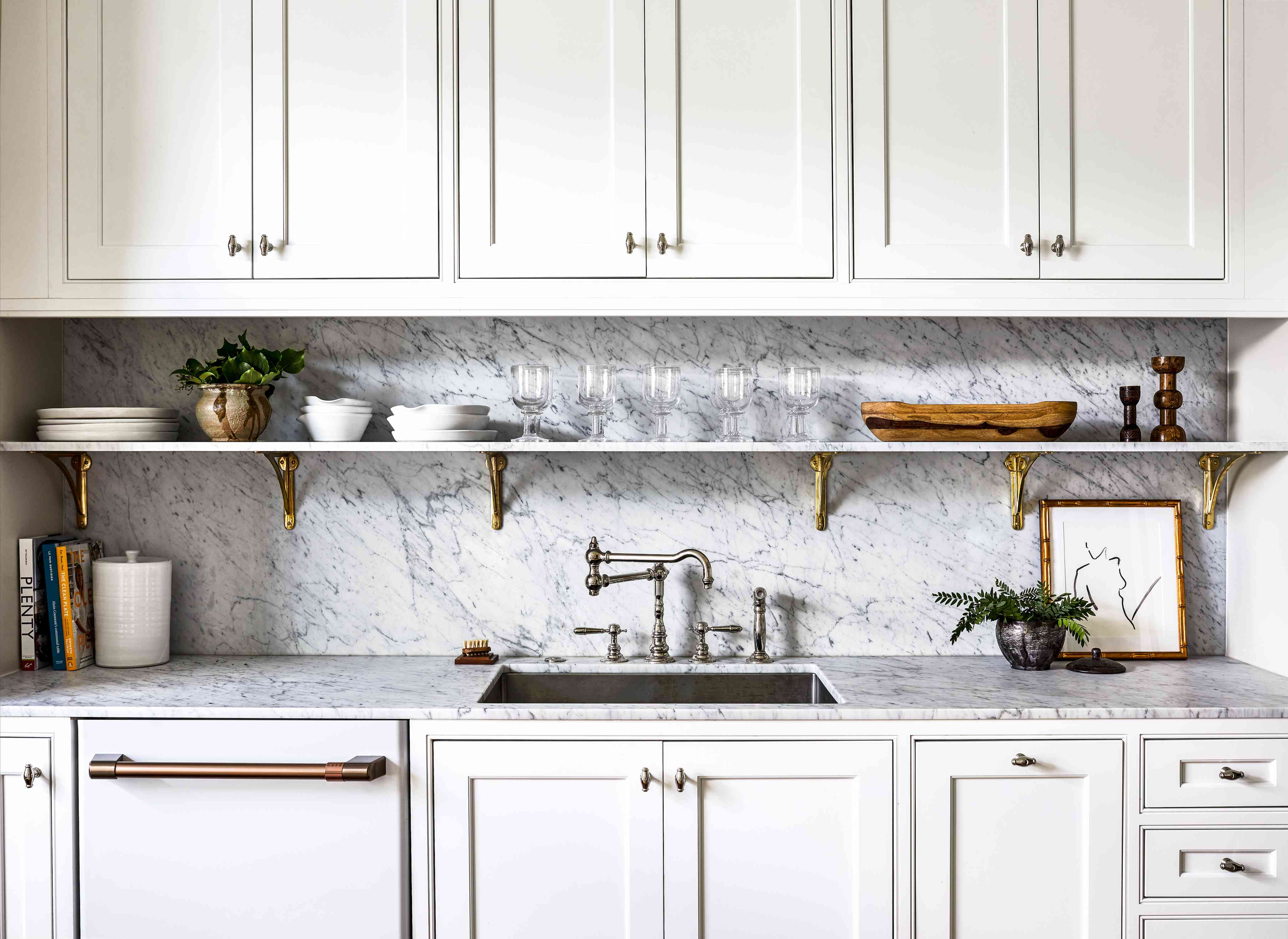 Close up of marble kitchen counters and shelf with glassware.