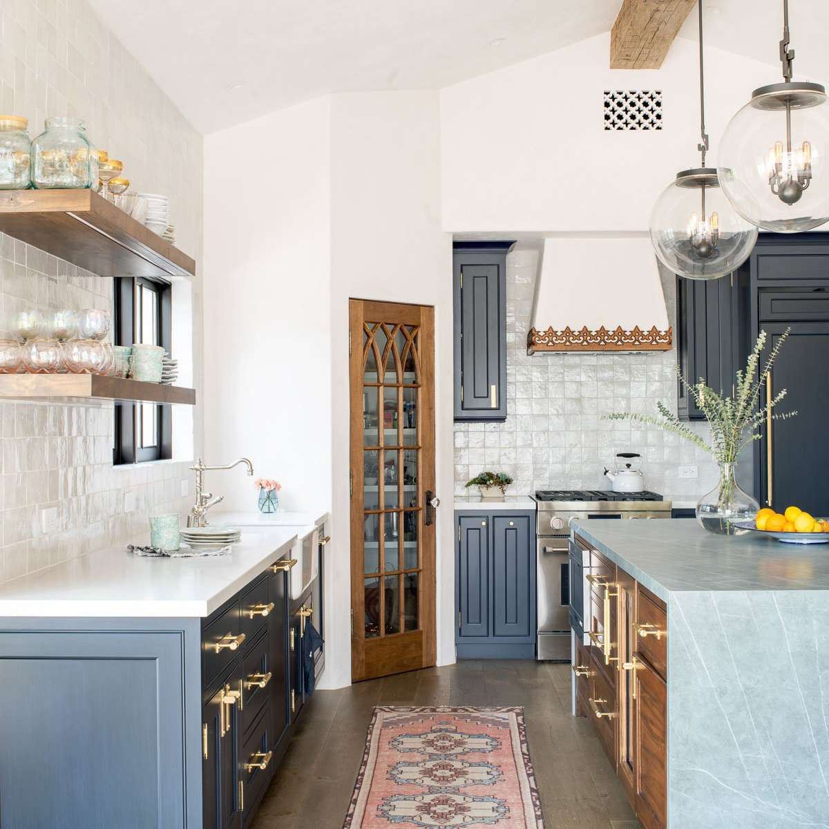 A kitchen with navy cabinets, marble countertops, and a pink rug