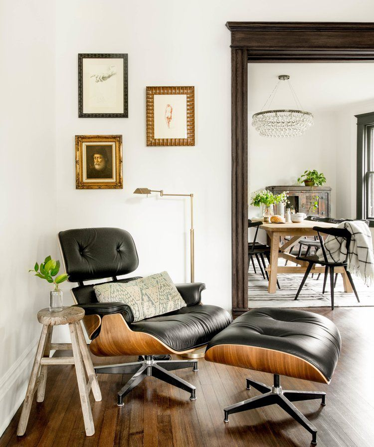 A corner decorated with a modern lounge chair, a rustic side table, and three pieces of antique art