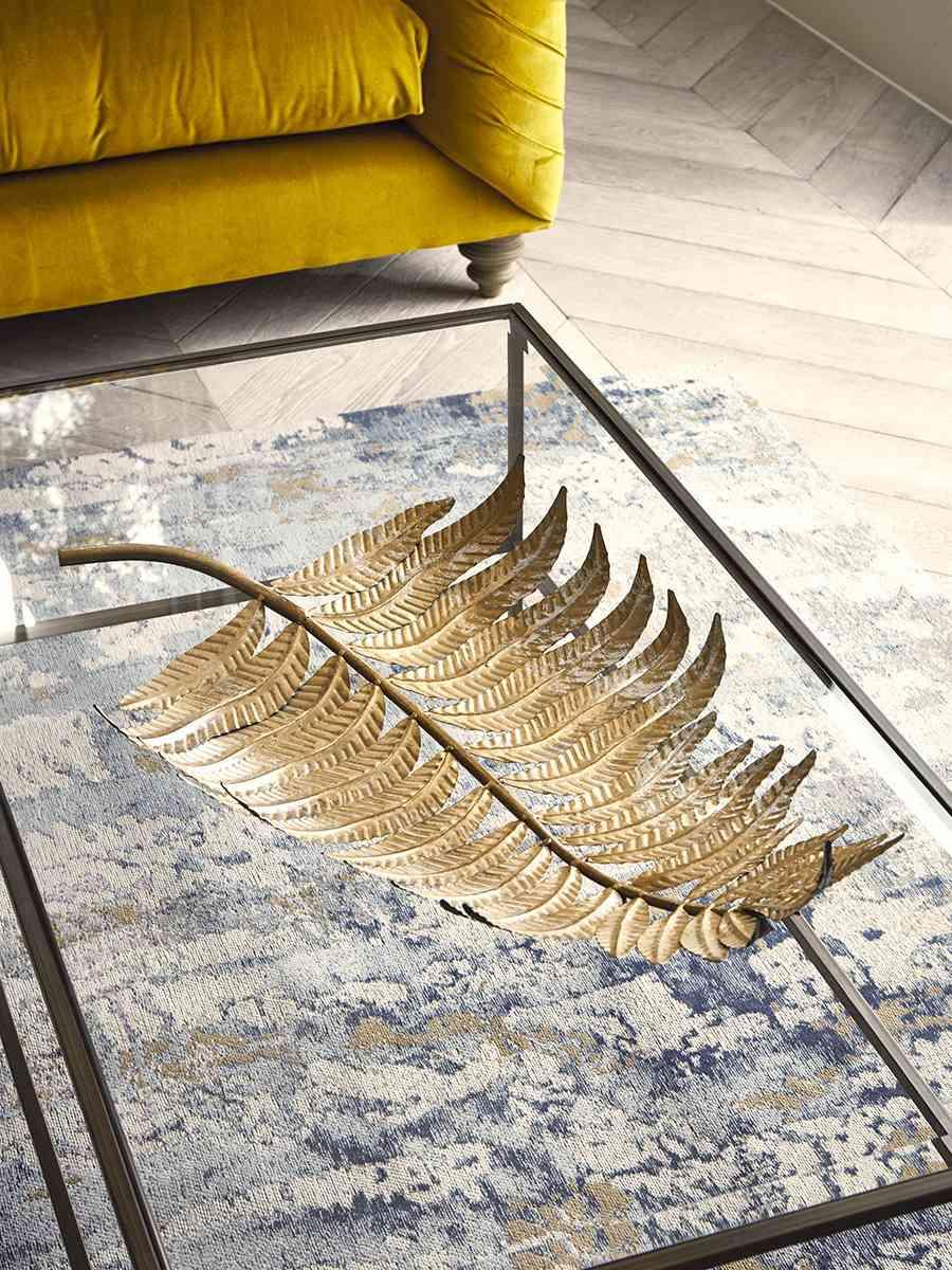 A brass-tone decorative dish that looks realistically like a large fern leaf.