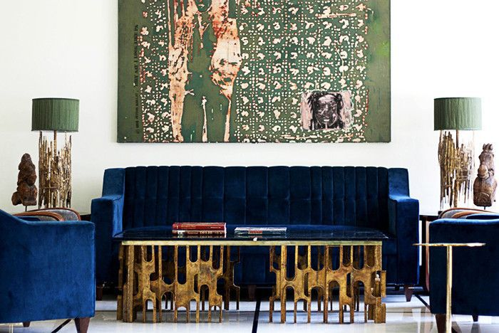 Brutalist living room with blue velvet sofa and organic bronze coffee table