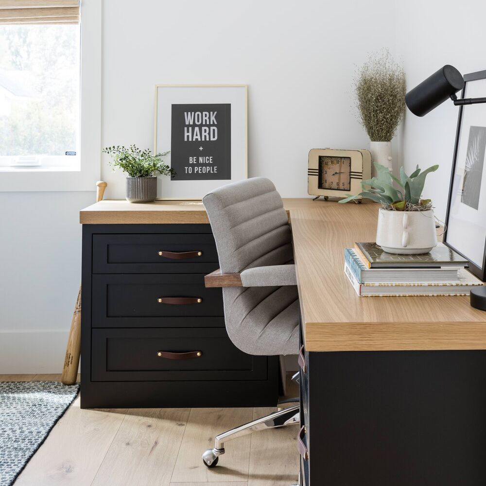 A home office with a wraparound wooden desk, a comfy rolling chair, and neutral decor