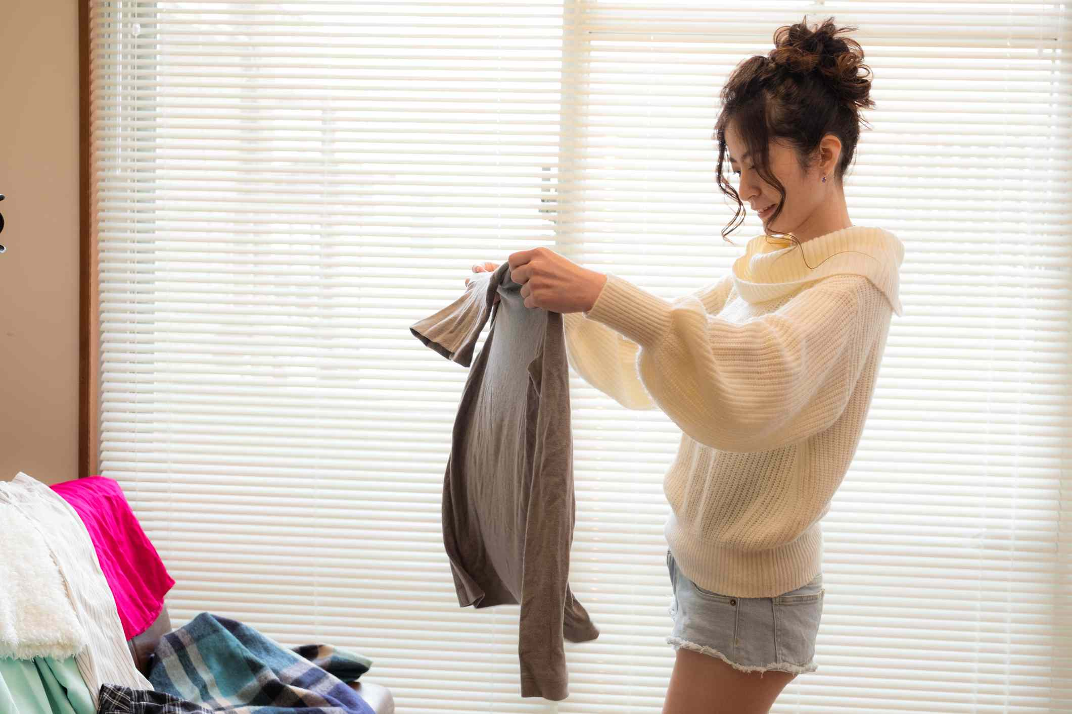 Woman holds up long sleeved shirt above pile of clothes