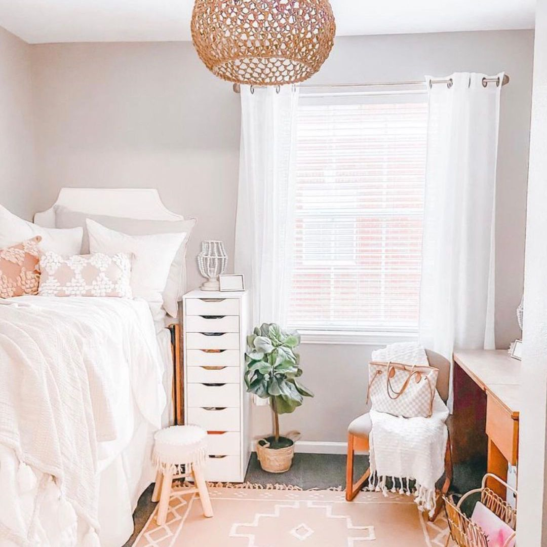 Well decorated dorm room with rattan chandelier and plant.
