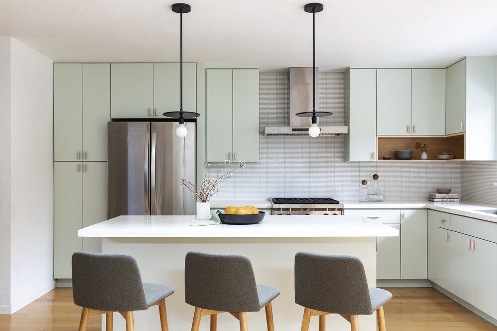 A kitchen with mint cabinets and very skinny backsplash tiles