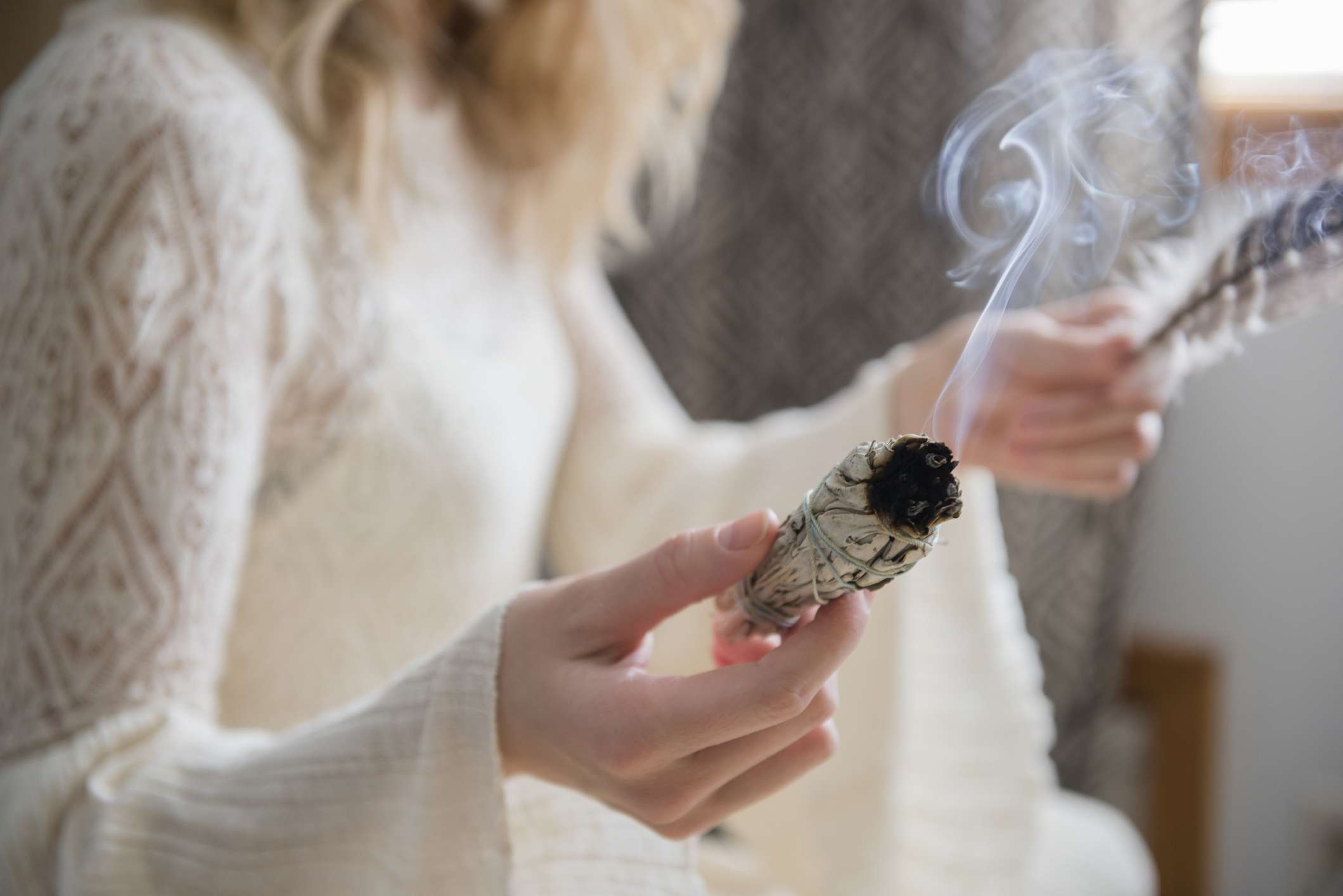 Woman holds bundle of sage to smudge room