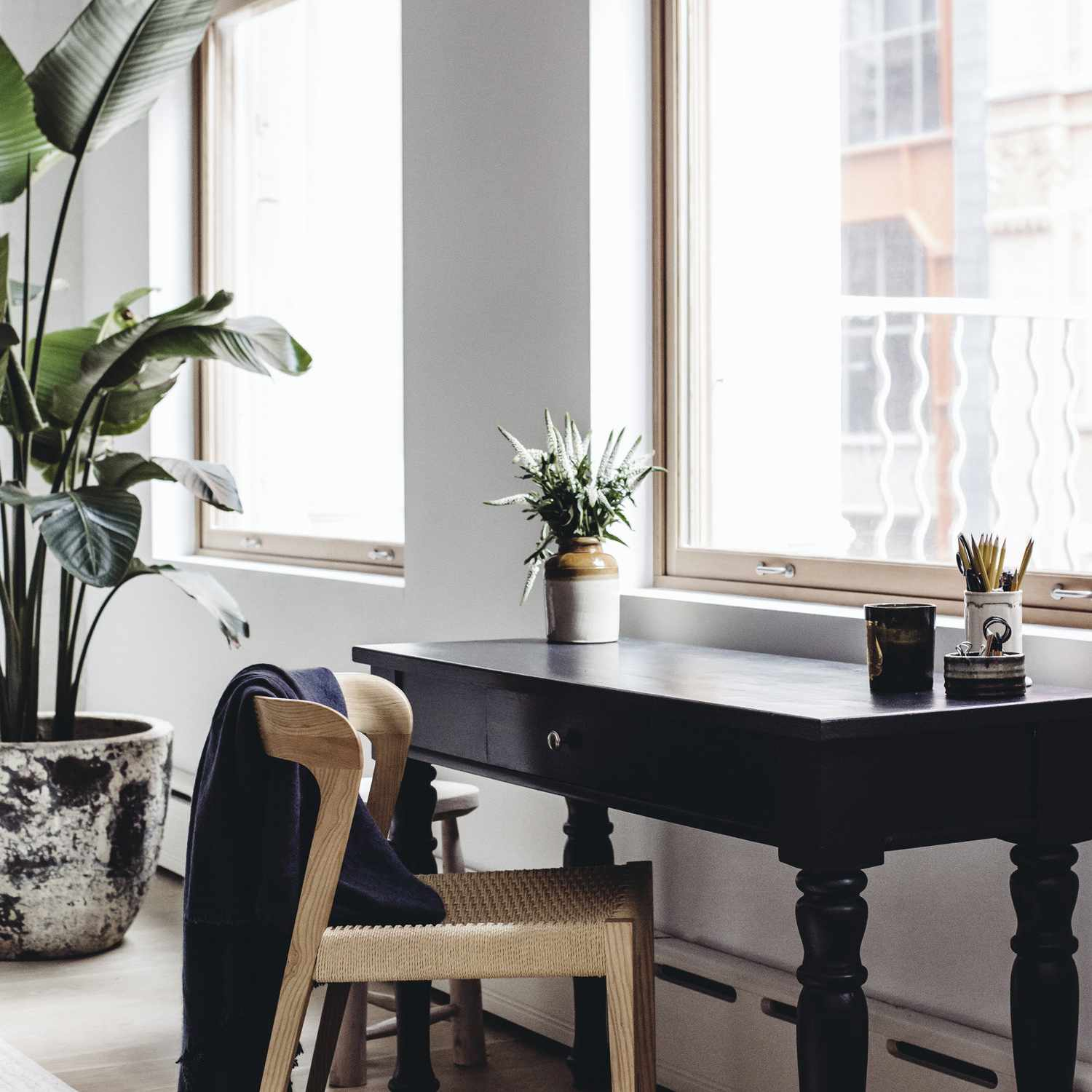 A small window-side workspace made up of a black wooden desk and a tan wooden chair