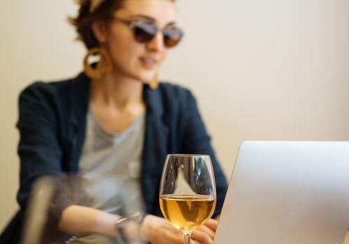 woman with wine at her laptop