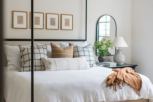 Cozy bedroom with canopy bed and neutral bedding.