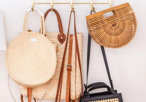 Woven bags hanging from bamboo rack.