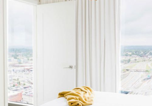 Natural light filters into all-white bedroom with chandelier