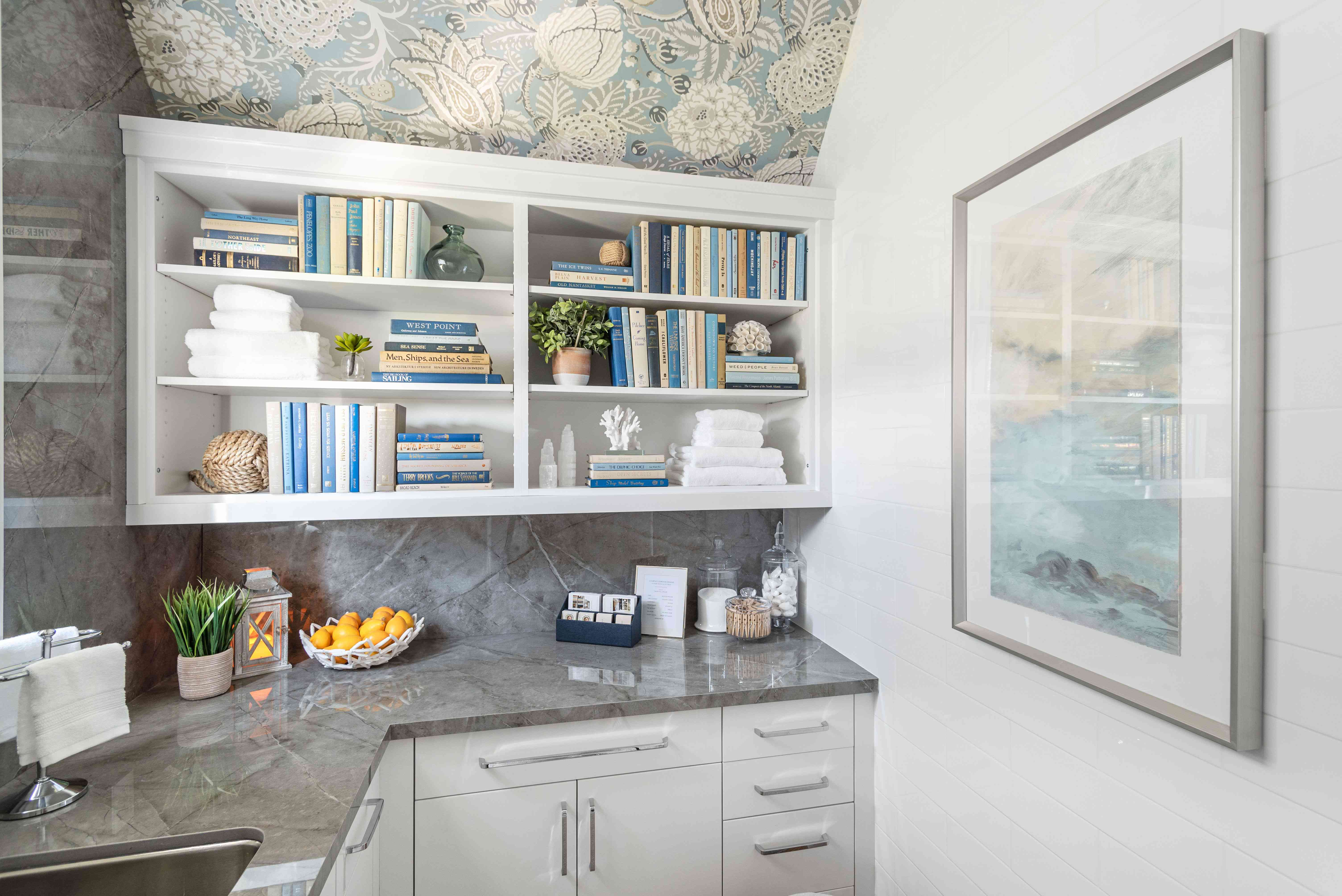 Laundry room nook with decorative books and wallpaper.