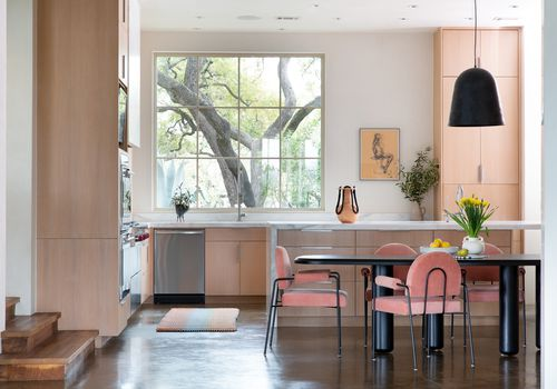 Sunny kitchen with pink velvet dining chairs.
