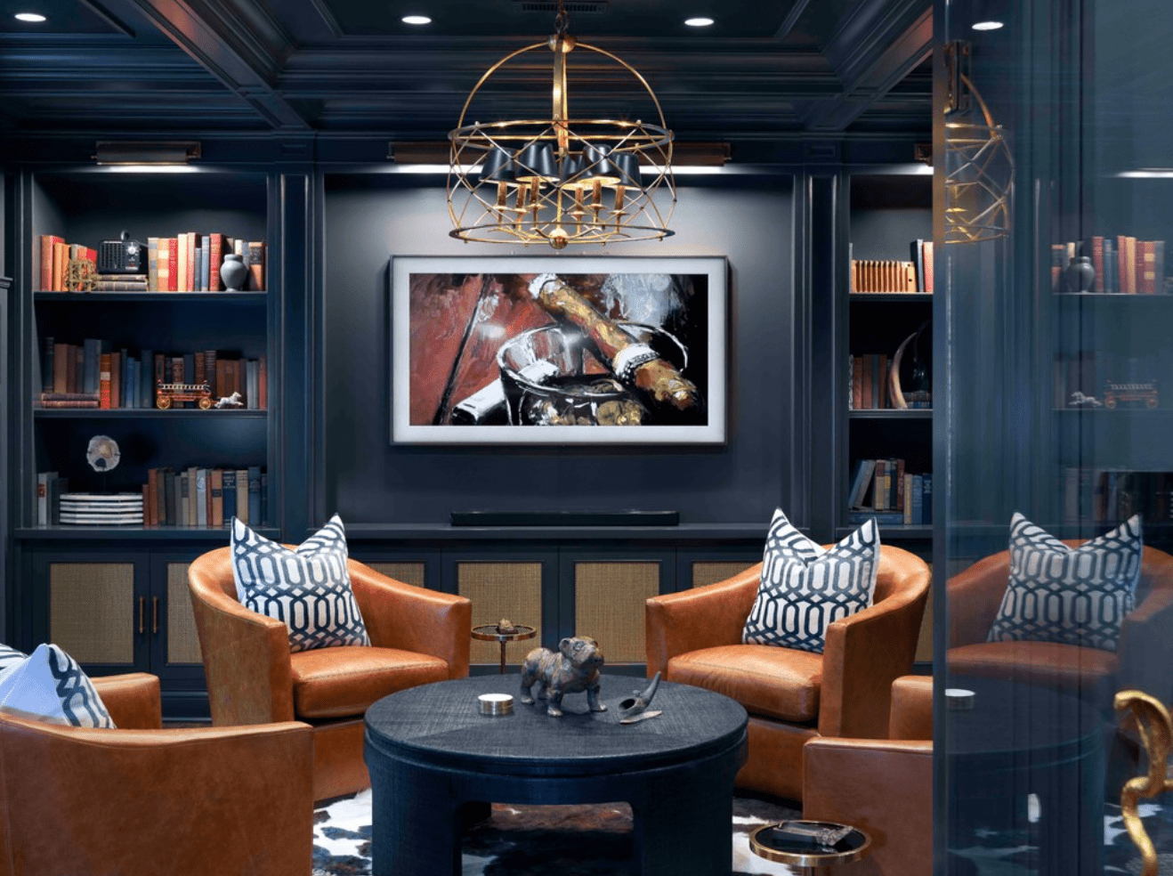 A cozy basement lit with recessed lighting, a chandelier, a picture lights mounted on bookshelves