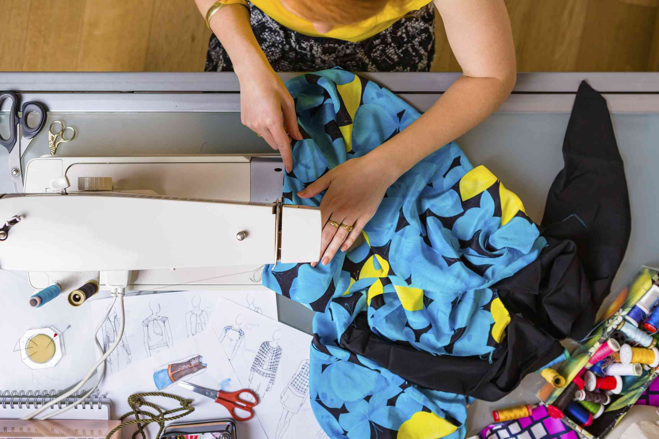 Woman works with sewing machine and patterned fabric